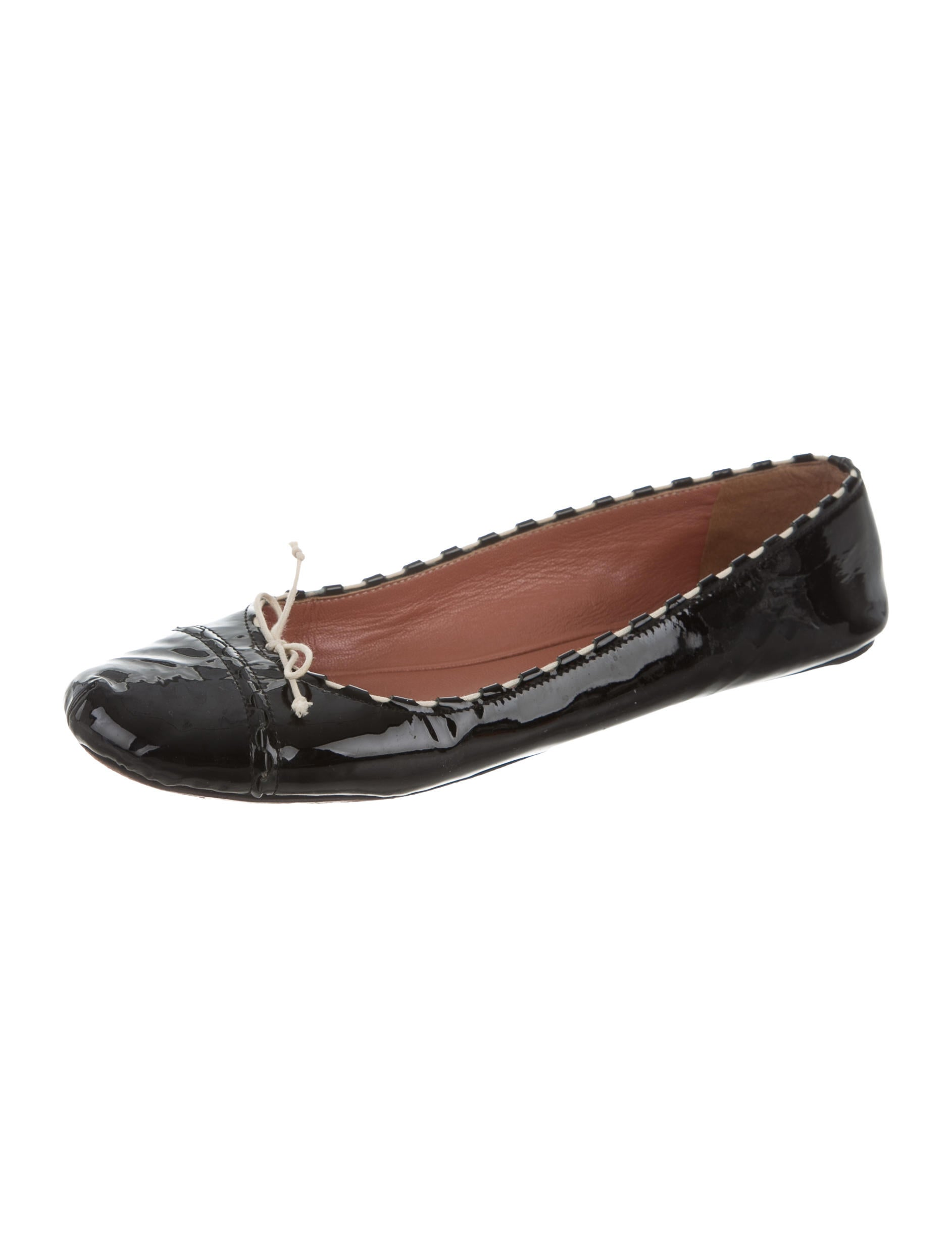 Patent finish ballet flat with die-cut detail. Adjustable buckle strap closure on the side with a decorative buckle on the upper. Fabric interior lining and insole.